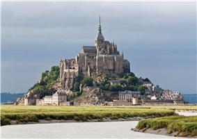 The buildings of Mont Saint Michel sit on a rocky island that rises above the surrounding fields and bay