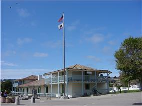 Photograph of the Old Customhouse in Monterey, a two-story Spanish-colonial structure with broad verandahs, tile roofs, blue and green trim, and white stucco.