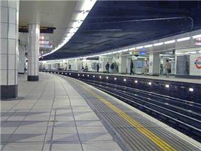 The interior of a building with a railway track running between white-tiled pillars upholding a white-and-black ceiling lit by electrical lights