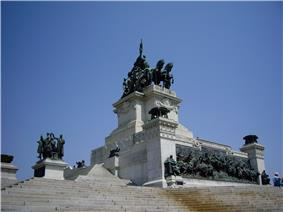 Photograph of a white stone steps leading up to a large, altar-like monument in white marble with bronze sculptural decorations that include bronze braziers at the corners, a bronze frieze in high relief at the base and bronze figures surrounding a chariot on a high, white marble plinth in the center