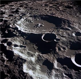 A grey, many-ridged surface from high above. The largest feature is a circular ringed structure with high walled sides and a lower central peak: the entire surface out to the horizon is filled with similar structures that are smaller and overlapping.