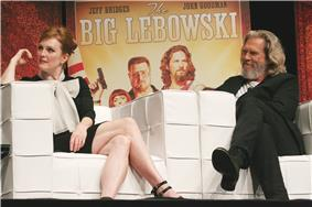 Julianne Moore and Jeff Bridges sitting down in front of a poster of The Big Lebowski