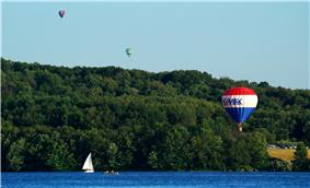 Three hot air balloons over a lake with a sailboat and forested shore