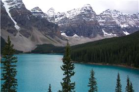 Lake and forest in front of high rocky mountains with snow.