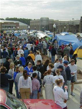 A large group of individuals gather in a parking lot alongside a tent campground with lightposts