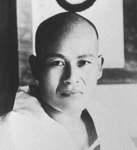 Portrait of a young Japanese man with a shaved head staring into the camera