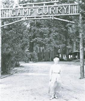Woman in a long dress in front of a sign across a road. Wooden letters read