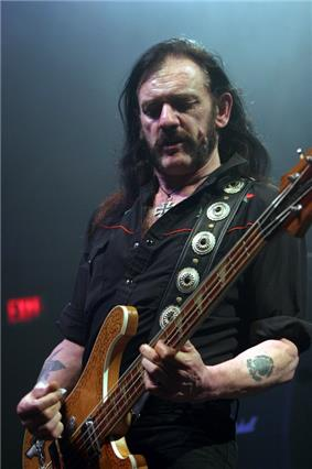 A man wearing a black shirt, looking down and playing a bass guitar.