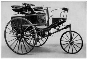 A black-and-white photograph shows a small open-air vehicle with three wheels, each spoked like bicycle tires. Visible are a small seat, a crank for steering, and a hand throttle for acceleration.