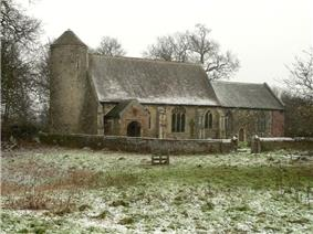 A mainly stone church with a round tower on the left, to the right is a nave with a porch, and a chancel at a lower level