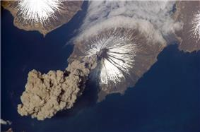 A thick plume of dark ash arises from the volcano's cone.