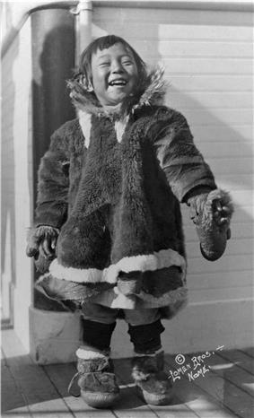 A small child standing on what appears to be a ship's deck. She is wearing a fur smock and fur boots, and has an open, happy expression.