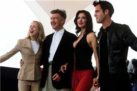Four people stand beside each other facing off-camera, from left to right: a blonde woman wearing a tan dress suit, a man with salt-and-pepper hair wearing a blazer over white shirt and slacks, a brunette wearing red pants and a black top, and a dark-haired man wearing a black leather jacket over black clothes.