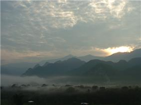 Sunset or sunrise over a mountain landscape with fog in the valleys.