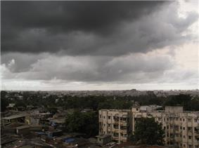 Daytime view over a city: de-laminating concrete housing blocks surrounded by rough slum tenements. In the middle distance, an expanse of trees: perhaps a park. Near the horizon, the largely concrete structures that compose the city continue. The whole is enveloped by an ominous sky filled with storm clouds promising imminent heavy rain.