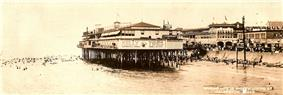 A black-and-white postcard shows a photograph, taken from a location on the water, of a large building sitting on pier by the beach. The beach is fronted by a seawall and a crowded waterfront beyond. The caption on the postcard says
