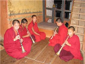 Monks playing lingm at Lhuentse Dzong