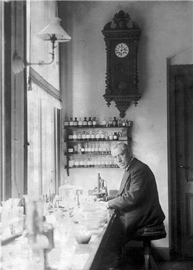 An old, bespectacled man wearing a suit and sitting at a bench by a large window. The bench is covered with small bottles and test tubes. On the wall behind him is a large old-fashioned clock below which are four small enclosed shelves on which sit many neatly labelled bottles.