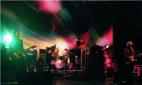 MBV performing live on stage against a green and red backdrop.