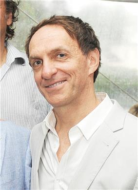 A Canadian male in his mid-fifties is seen wearing an unbuttoned, white collared shirt under a white coat.