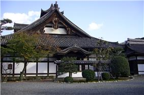 Wooden building with white walls and hip-and-gable style roof.