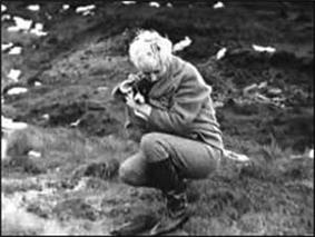 A crouched blonde woman in thick jacket, trousers, and boots, holding a small dog.