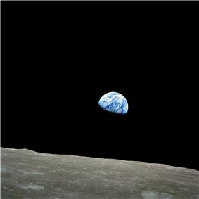 The small blue-white semicircle of Earth, almost glowing with colour in the blackness of space, rising over the limb of the desolate, cratered surface of the Moon.