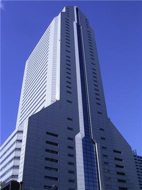 Ground-level view of a light blue high-rise; one flat facade is bisected by a column of glass, while the adjacent facades angle in at several points until they meet at a point at the top