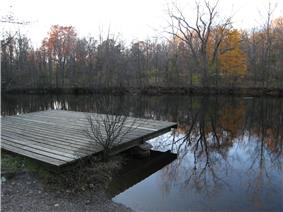 A wooden dock on the shore of a small lake in which autumnal trees are reflected