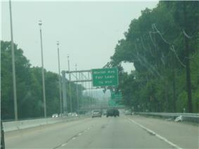 A four lane highway with a center concrete barrier containing lampposts that is surrounded by trees and has power lines running along its right side. A green overhead sign in the distance reads Morlot Ave. Fair Lawn 1/4 mile.