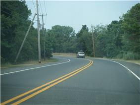 A two lane road lined with power lines making a curve through woodland