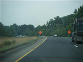 A four lane freeway running through a wooded area