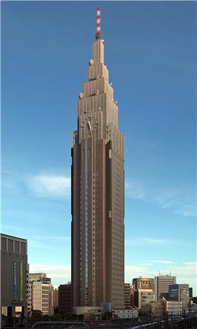 Ground-level view of a brown, rectangular high-rise; as it rises, it terraces to a point and a white and an orange antenna rises from the top. A clock is located on one side of the building.