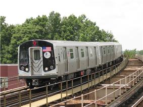 A train made of R160 cars in J service arriving at 104th Street, bound for Jamaica Center.