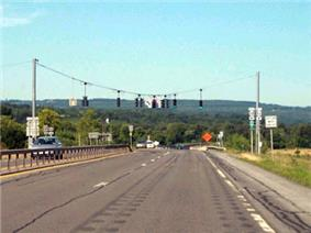 A view of the four-lane NY 5S as it approaches a traffic signal. NY 28 is accessed by turning left at the signal. In the background and distance are tree-covered mountains.