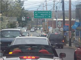 A narrow four-lane highway is jammed with cars as they wait at a signalized intersection.