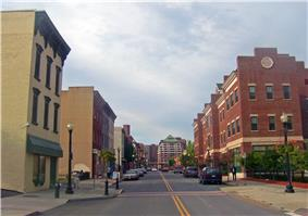 A two-lane city street is flanked on both sides by several multi-story buildings. Taller buildings are visible in the background.