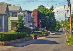 A narrow two-lane street is surrounded by houses on its left side.
