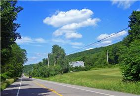 A two-lane highway lined with telephone poles passes through a rural, forested area. In the background is a tree-covered ridge.