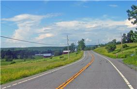 A two-lane highway in a sparsely developed and hilly area with two farm buildings nearby. Large mountain ridges are visible in the distance.