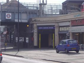 A beige building with a rectangular, dark blue sign reading