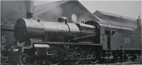 Side-and-front view of a modified version of the Nclass on shed. The distinguishing feature from normal Nclass locomotives is the tall cylindrical chimney on the smokebox. A member of the crew is standing next to the tender.