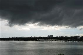 Dark storm clouds over a waterbody with buildings in the far background