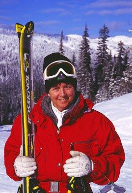 A woman smiles as she holds a pair of skis upright. She is wearing a thick red coat with white gloves and black toque.