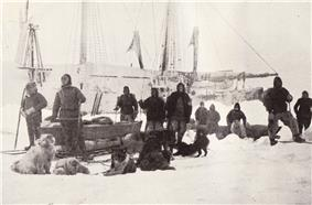 A group of men pose on the ice with dogs and sledges, with the ship's outline visible in the background