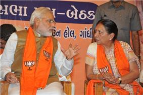 Modi talking to a woman; both are seated.