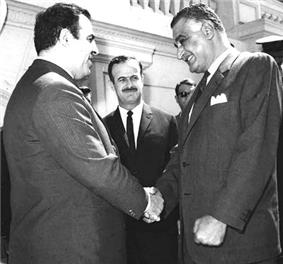 Two men shaking hands, with mustachioed man in background