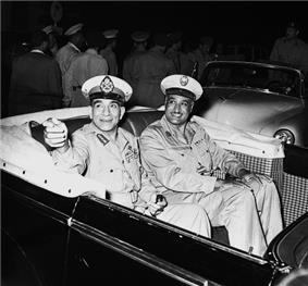 Two smiling men in military uniform seated in an open-top automobile. The first man on the left is pointing his hand in a gesture. Behind the automobile are men in uniform walking away from the vehicle