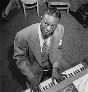 Black-and-white photograph of a bird's eye view of Nat King Cole as he plays an upright piano.