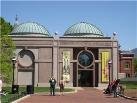 A one story symmetrical granite building with two green domed roofs either side of center. The entrance door is on the right and a similar design is on the left made out of a slightly darker granite.